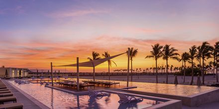 Poolen og smuk solnedgang på Fanar Hotel & Residences i Salalah, Oman.